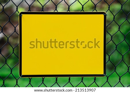 Blank yellow info plate hung on a wire fence - stock photo