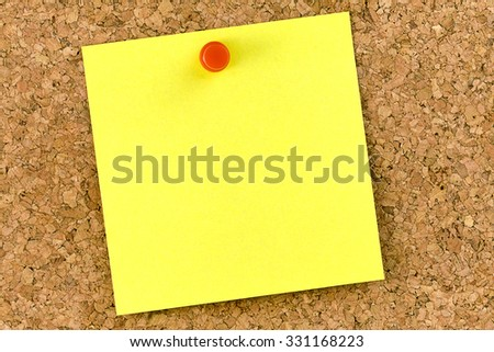 Blank yellow postit affixed on cork board with red thumbtack - stock photo