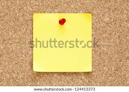 Blank yellow sticky note pinned on a cork bulletin board. - stock photo