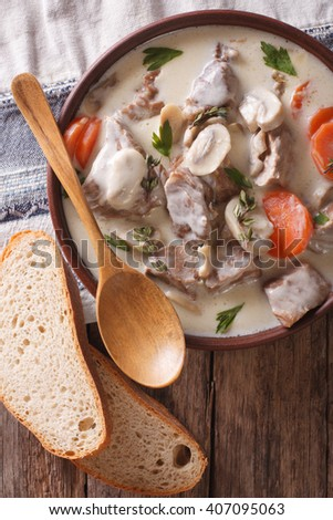 Blanquette of veal in a creamy sauce in a bowl on the table. vertical view from above - stock photo