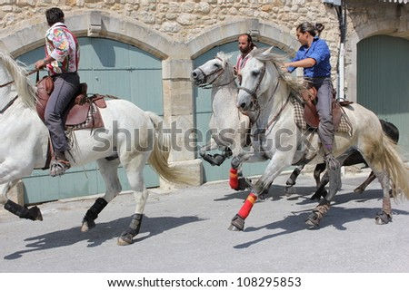 BLAUZAC, FRANCE - JUL 15: Herd of horses runs from the bulls in a street of Blauzac during village traditional summer festival on July 15, 2012 in Blauzac, Gard France. A festival called abrivado. - stock photo