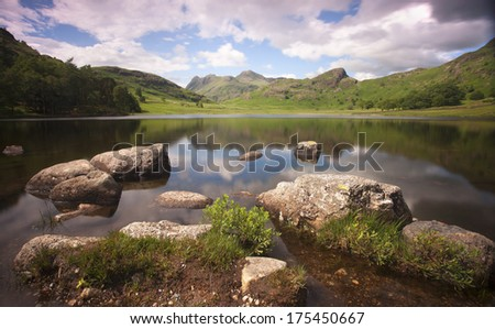 blea tarn mountains and lake with rocky foreground in cumbria - stock photo