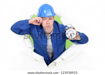 Bleary eyed construction worker with an alarm clock - stock photo