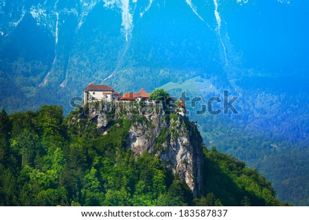 Bled castle on the cliff in Slovenia with high Alps on background - stock photo