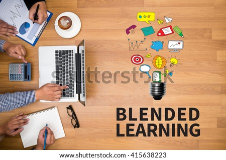 BLENDED LEARNING Business team hands at work with financial reports and a laptop - stock photo