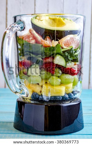 Blender filled with raw fruits and vegetables to make a green health smoothie - stock photo