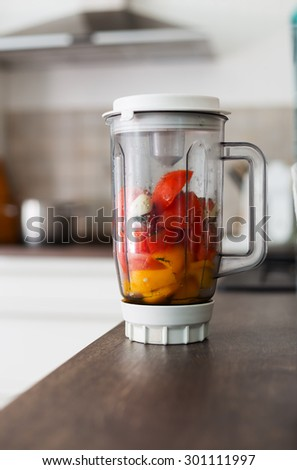 Blender with fresh vegetables on kitchen table - stock photo