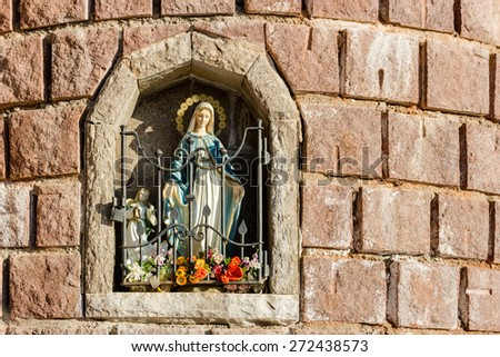 Blessed Virgin Mary statue in wall shrine with angel and fake flowers - stock photo