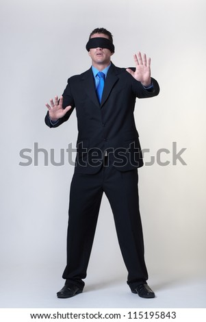 blind folded business man not knowing where to go - stock photo
