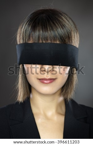 blind folded business woman low key lighting shot in the studio on a gray background - stock photo