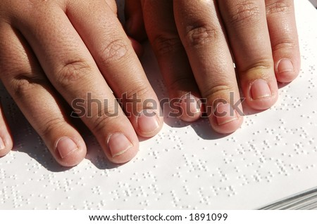 Blind person reading Bible written in Braille - stock photo