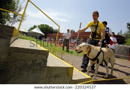 Blind person with his guide dog/Sofia, Bulgaria - June 25, 2014: A blind man is led by his guide dog trough stairways as part of dog's training.  - stock photo