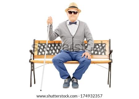 Blind senior man seated on bench isolated on white background - stock photo