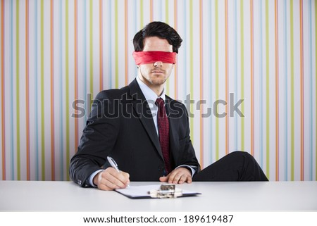 Blindfold businessman at his office signing contracts - stock photo