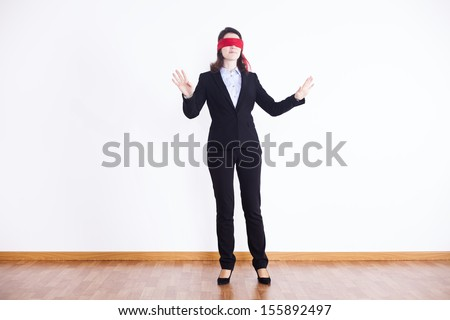 blindfold businesswoman trying to find something  - stock photo