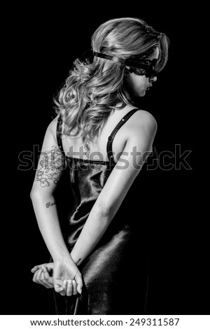 Blindfold woman with hands behind her back black and white - stock photo