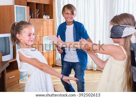 Blindfolded little girl catching cheerful kids playing in Kagome at home