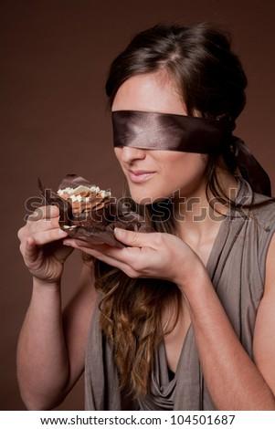 Blindfolded woman holding cake - stock photo