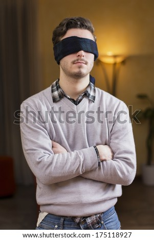 Blindfolded young man at home in living room cannot see - stock photo