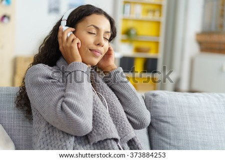Blissful attractive trendy young woman enjoying her music as she relaxes on a sofa in her living room listening to tunes on her headphones with her eyes closed smiling with enjoyment - stock photo