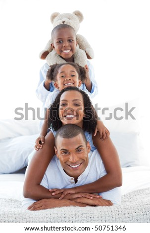 Blissful family having fun lying down on bed at home - stock photo