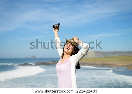 Blissful funky woman towards the sea enjoying freedom, tranquility and relax. Beautiful young happy female on coast travel feeling the ocean breeze. - stock photo