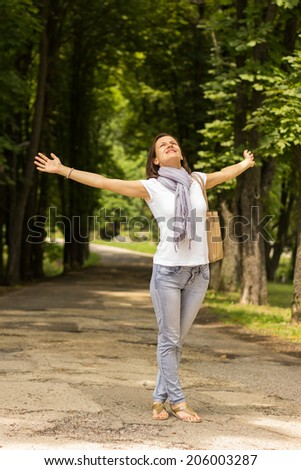 Blissful woman enjoying freedom and life in park on spring. - stock photo