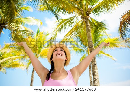 Blissful woman on tropical summer caribbean vacation raising arms to the sky with palm trees on background. Happy woman enjoying at the beach. - stock photo