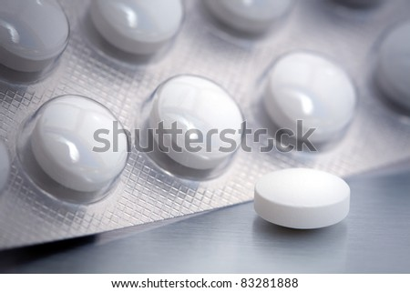 Blister pack of round white pills. One is out of the package. - stock photo
