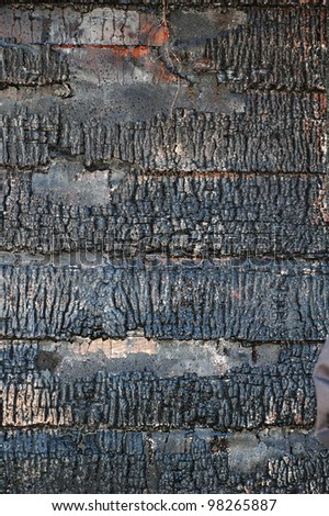 Blistered paint and charcoaling of wood siding following a structure fire - stock photo