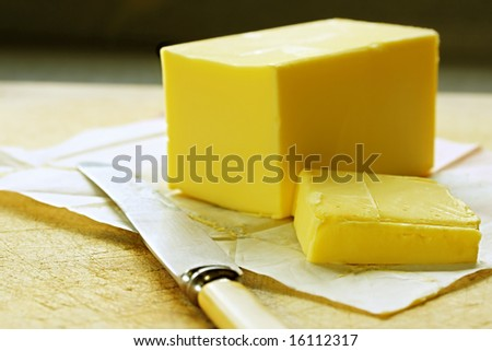 Block of butter, cut, on old chopping board, with bone-handled knife. - stock photo