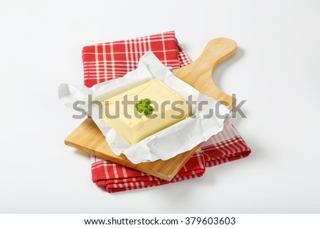 block of fresh butter on wooden cutting board - stock photo