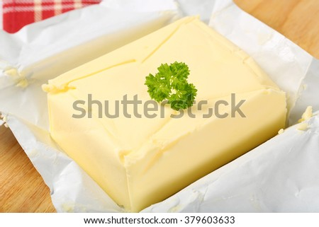 block of fresh butter on wooden cutting board - detail - stock photo