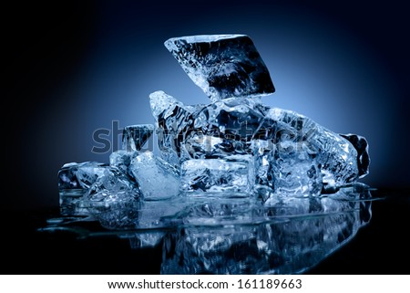 Block of frozen ice with blue toned background. - stock photo