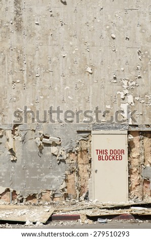 Blocked exit door on a building being remodeled but looks like a blast or war zone - stock photo