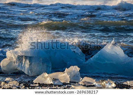 Blocks of ice from the glaciers break up and is washed ashore by the strong waves of the North Atlantic sea in Iceland. - stock photo