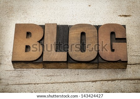 blog - a word in vintage letterpress wood type on a grunge painted barn wood background - stock photo