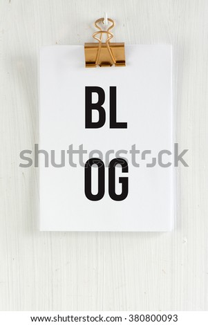 Blog Clipboard, conceptual communication. on white wooden background and golden clip. - stock photo