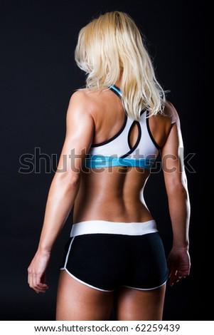 Blond athlete isolated on black - stock photo