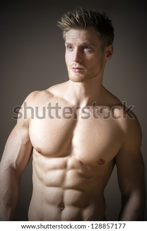 Blond, athletic man with blue eyes and a muscular upper body - stock photo