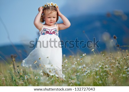 Blond baby girl in wreath in field of camomiles - stock photo