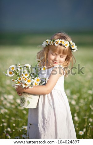 Blond baby girl in wreath in field of chamomiles - stock photo
