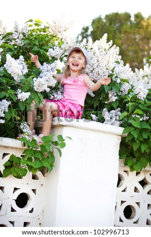 Blond baby girl sitting on fence at lilac, singing song and swinging arms - stock photo
