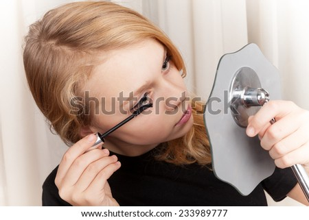 Blond beautiful Caucasian girl in black paints eyelashes with mascara - stock photo