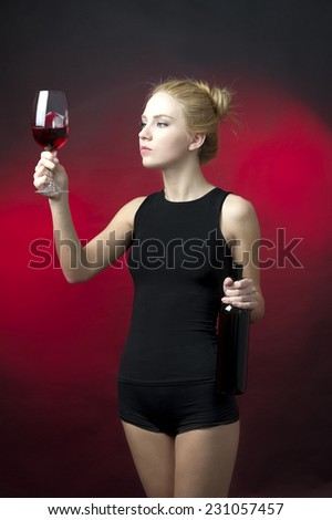 blond beauty model holding bottle and wineglass and checking the color of red wine looking into glass - stock photo