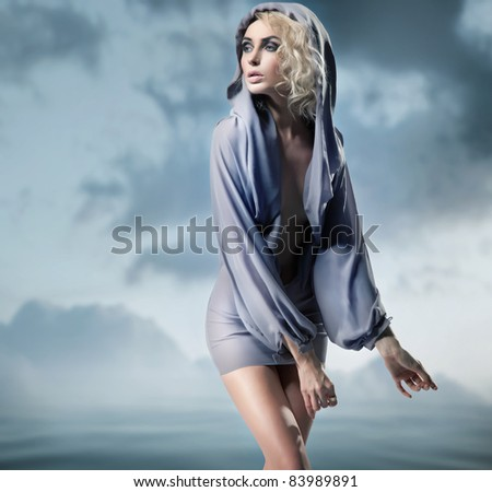 Blond beauty posing over dark sky - stock photo