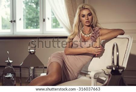 Blond beauty sitting on stylish sofa - stock photo
