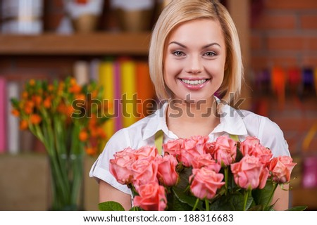 Blond beauty with bunch of roses. Attractive young blond hair woman in apron holding bunch of roses and smiling - stock photo