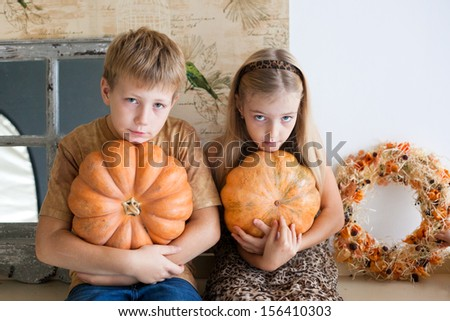 blond boy and girl studio portrait with pumpkins - stock photo