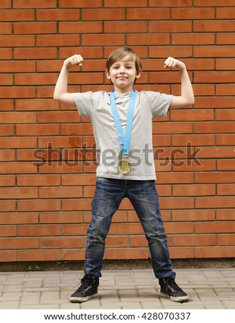 blond boy is happy gold medal - champion, winner - stock photo